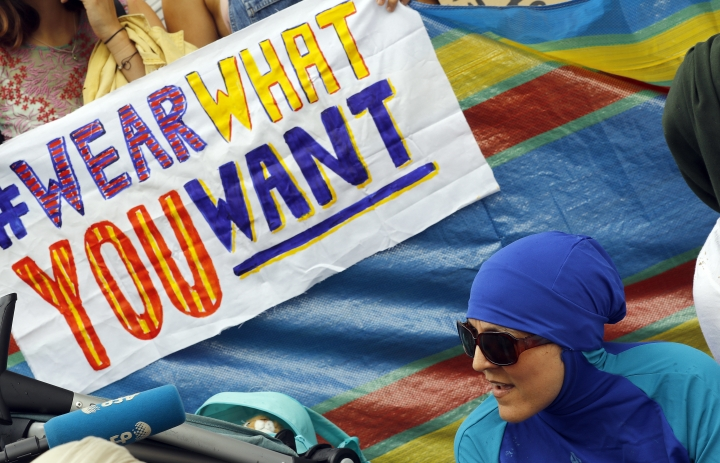 "An activist protests outside the French embassy during, the ""wear what you want beach party"" in London, Thursday, Aug. 25, 2016. The protest is against the French authorities clampdown on Muslim women wearing burkinis on the beach. (AP Photo/Frank Augstein)"