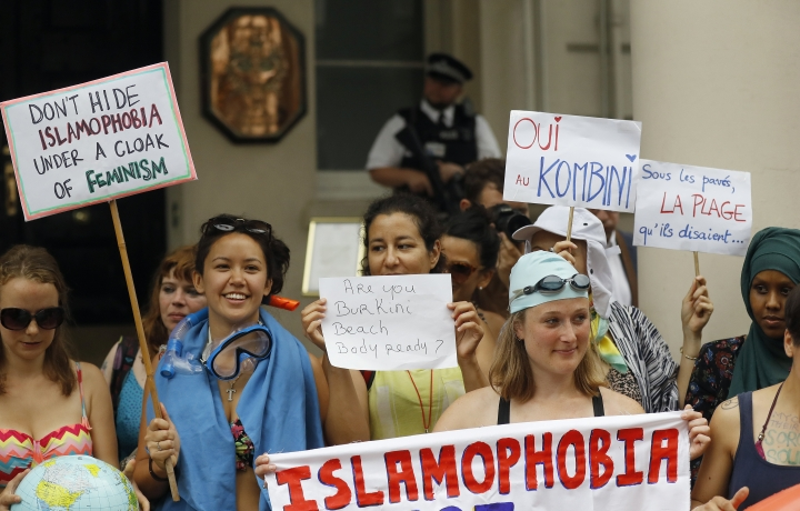 """Activists protest outside the French embassy during, the """"wear what you want beach party"""" in London, Thursday, Aug. 25, 2016. The protest is against the French authorities clampdown on Muslim women wearing burkinis on the beach. (AP Photo/Frank Augstein)"""