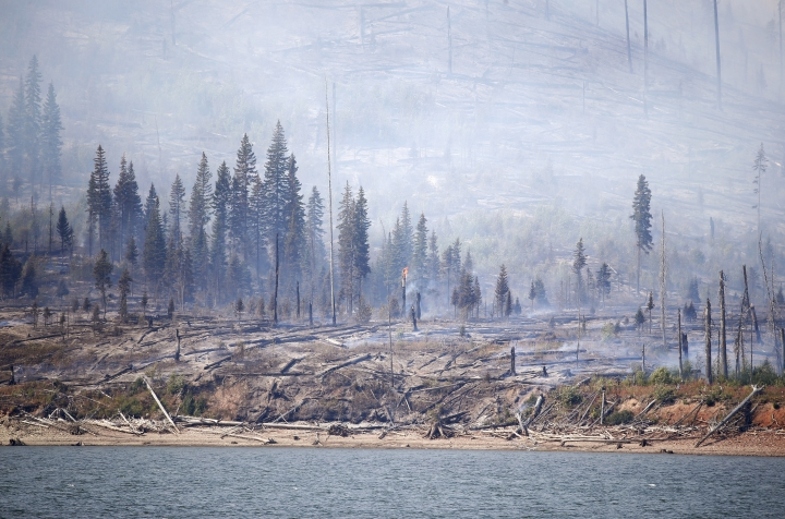The Berry Fire burns off the shore of Jackson Lake in Grand Teton National Park, Wyo., Thursday, Aug 25, 2016. Popular areas in Yellowstone and Grand Teton National Parks were welcoming tourists Thursday for the 100th anniversary of the National Park Service, but a wildfire forced some people to drive a little farther than they expected. The blaze in Grand Teton National Park shut down a route leading to Yellowstone's South Entrance, so visitors coming from the south through Wyoming had to take a detour into Idaho. (AP Photo/Brennan Linsley)