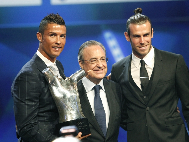 "Real Madrid's forward Cristiano Ronaldo of Portugal, left, holds his ""best player of the year"" trophy, as he poses with Real Madrid's forward Gareth Bale, right, who was nominated for the same award, and Real Madrid's president Florentino Perez, during the UEFA Champions League draw, at the Grimaldi Forum, in Monaco, Thursday, Aug. 25, 2016. (AP Photo/Claude Paris)"