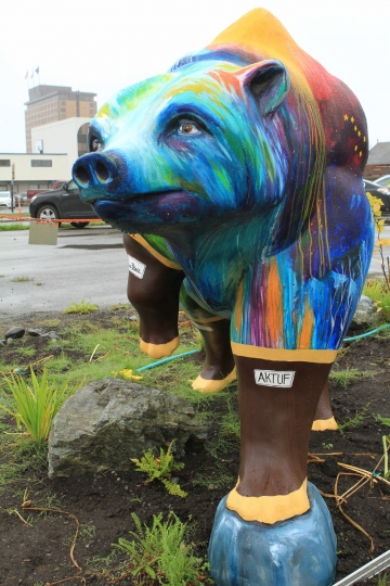 "A life-size, fiberglass bear statue painted with nature scenes and rubber boots, part of a ""Parade of Bears"" display, stands in front of offices of Great Land Trust on Thursday, Aug. 25, 2016, in Anchorage, Alaska. The statues were installed to increase awareness of grizzly and black bears that live within the municipality of Anchorage and to highlight an international bear conference hosted by the city. (AP Photo/Dan Joling)"