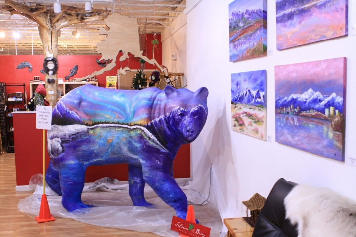 """A life-size, fiberglass bear statue painted with colors of the aurora stands inside Salmon Berry Tours on Thursday, Aug. 25, 2016, in Anchorage, Alaska. Bear statues, part of """"Bears on Parade,"""" were installed to increase awareness of brown and black bears that live within the municipality of Anchorage and to highlight an international bear conference hosted by the city. (AP Photo/Dan Joling)"""