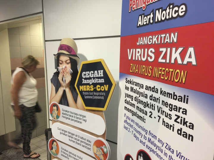 A traveller walks past a travel advisory on the Zika virus infection in Kuala Lumpur International Airport in Sepang, Malaysia, Sunday, Aug. 28, 2016. According to local reports, Singapore Ministry of Health (MOH) and National Environment Agency informed a Malaysian woman living in Singapore became the first patient to be infected by locally-transmitted Zika virus. (AP Photo/Vincent Thian)