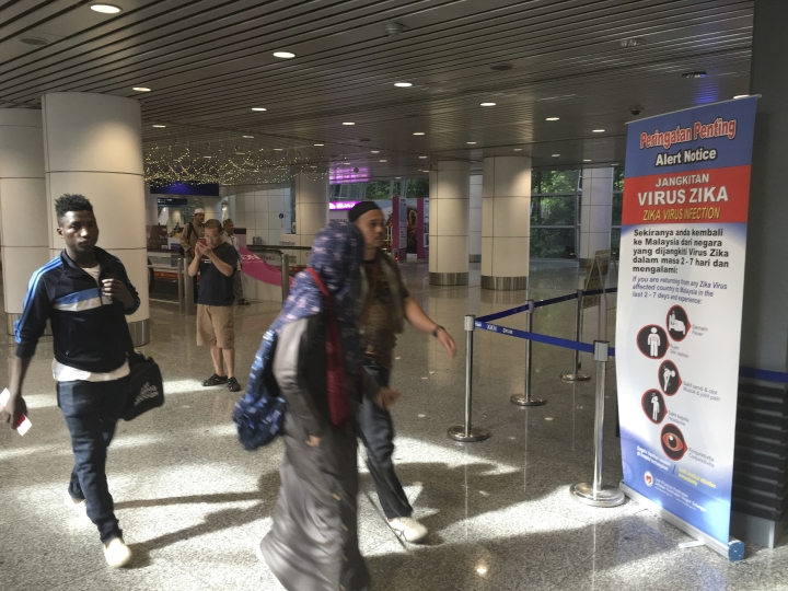 Travelers walk past a travel advisory on the Zika virus infection in Kuala Lumpur International Airport in Sepang, Malaysia, Sunday, Aug. 28, 2016. According to local reports, Singapore Ministry of Health (MOH) and National Environment Agency informed a Malaysian woman living in Singapore became the first patient to be infected by locally-transmitted Zika virus. (AP Photo/Vincent Thian)