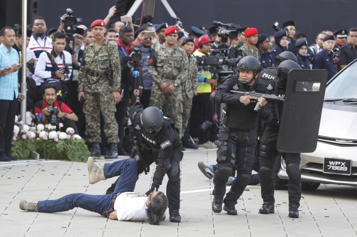 Malaysia's Special Task Force police personnel demonstrate subduing a terrorist scenario during the 59th National Day celebrations at the Independence Square in Kuala Lumpur, Malaysia on Wednesday, Aug. 31, 2016. (AP Photo/Joshua Paul)
