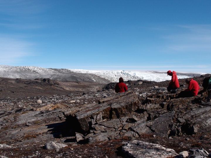 In this photo provided by Laure Gauthiez, taken in July 2012, a field team examine rocks in Greenland. Scientists have found what they think is the oldest fossil on Earth, a remnant of life from 3.7 billion years ago when Earth's skies were orange and its oceans green. In a newly melted part of Greenland, Australian scientists found the leftover structure from a community of microbes that lived on an ancient seafloor, according to a study in Wednesday, Aug. 31, 2016 journal Nature. (Laure Gauthiez/The Australian National University via AP)