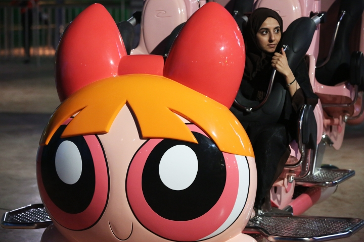 A woman waits for the Powerpuff Girls - Mojo Jojo's Robot Rampage ride to begin at the IMG Worlds of Adventure amusement park in Dubai, United Arab Emirates, on Wednesday, Aug. 31, 2016. in Dubai, United Arab Emirates, on Wednesday, Aug. 31, 2016. The IMG Worlds of Adventure indoor theme park opened Wednesday in Dubai, hoping to draw thrill seekers to its air-conditioned confines. (AP Photo/Jon Gambrell)