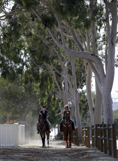 In this Thursday, Aug. 4, 2016 photo, two women on horseback ride near downtown in Norco, Calif. The Southern California city has rejected plans for a proposed Hindu cultural center partly because officials say the large, domed building doesn't fit in with its Old West-style motif. The decision last month by the city of Norco has riled some Indian-Americans who say the move was discriminatory. (AP Photo/Chris Carlson)