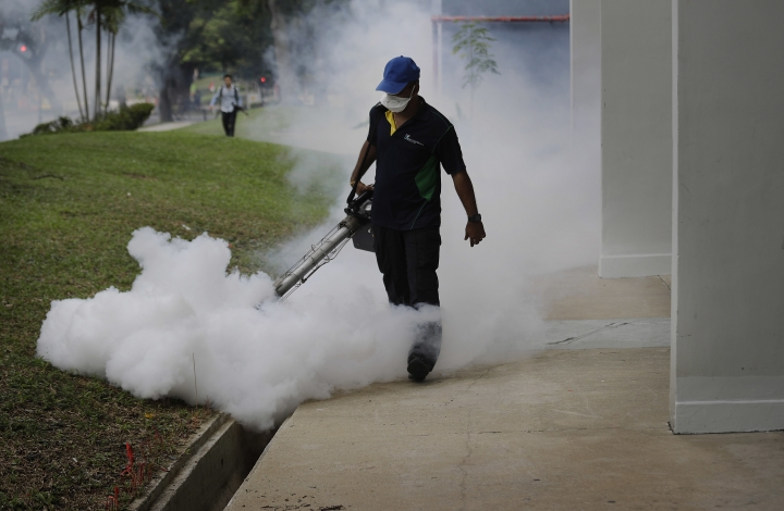 A pest control worker fumigates drains at a local housing estate where the latest case of Zika infections were reported from on Thursday, Sept. 1, 2016 in Singapore. Singapore issued a statement on Wednesday evening saying it had identified 22 new Zika cases in one particular area of the city and its first case involving a pregnant woman. (AP Photo/Wong Maye-E)