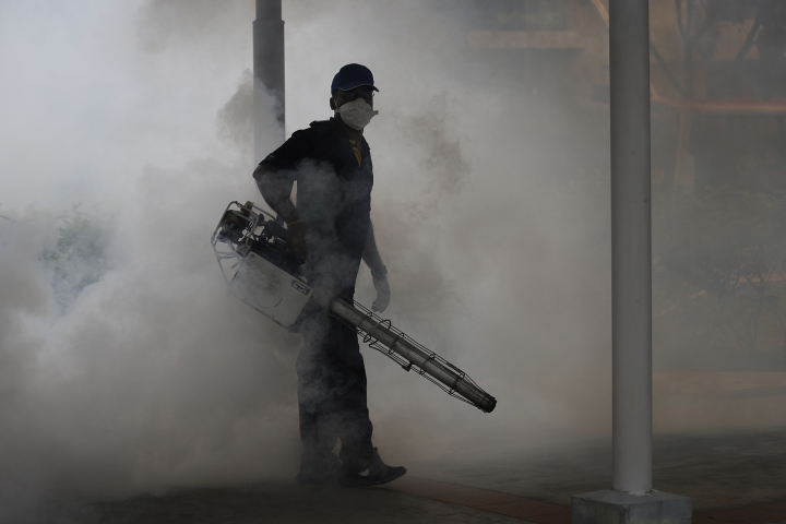 A pest control worker fumigates drains at a local housing estate where the latest case of Zika infections were reported on Thursday, Sept. 1, 2016, in Singapore. Indonesia is screening travelers from neighboring Singapore for the mosquito-borne Zika virus as the city-state reports a growing number of infections and its first case of a pregnant woman testing positive. (AP Photo/Wong Maye-E)
