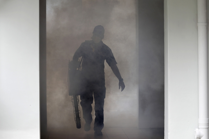 A pest control worker fumigates the ground floor of a local housing estate where the latest case of Zika infections were reported from on Thursday, Sept. 1, 2016, in Singapore. Indonesia is screening travelers from neighboring Singapore for the mosquito-borne Zika virus as the city-state reports a growing number of infections and its first case of a pregnant woman testing positive. (AP Photo/Wong Maye-E)