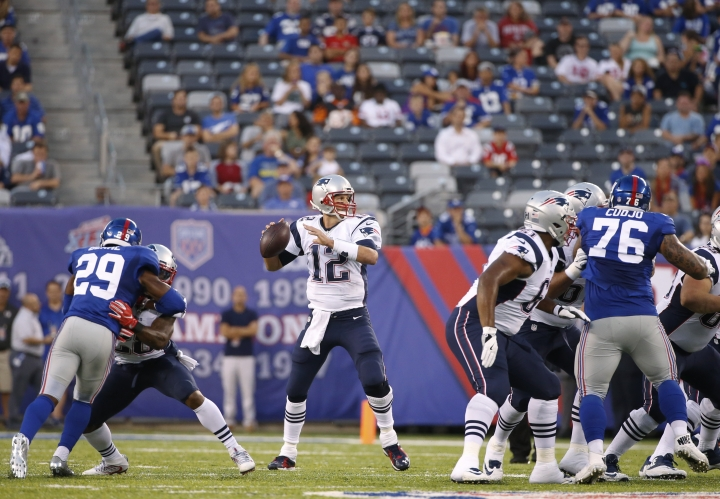 New England Patriots quarterback Tom Brady (12) looks to pass as New York Giants strong safety Nat Berhe (29) and Jermelle Cudjo (76) rush during the first half of a preseason NFL football game Thursday, Sept. 1, 2016, in East Rutherford. Brady was intercepted on the play. (AP Photo/Kathy Willens)