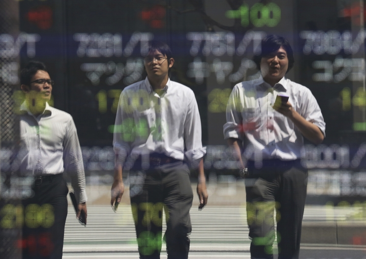 People are reflected on the electronic board of a securities firm in Tokyo, Friday, Sept. 2, 2016. Most Asian markets were listless Friday as investors awaited key U.S. job data that could influence the Fed's interest rate policy. (AP Photo/Koji Sasahara)