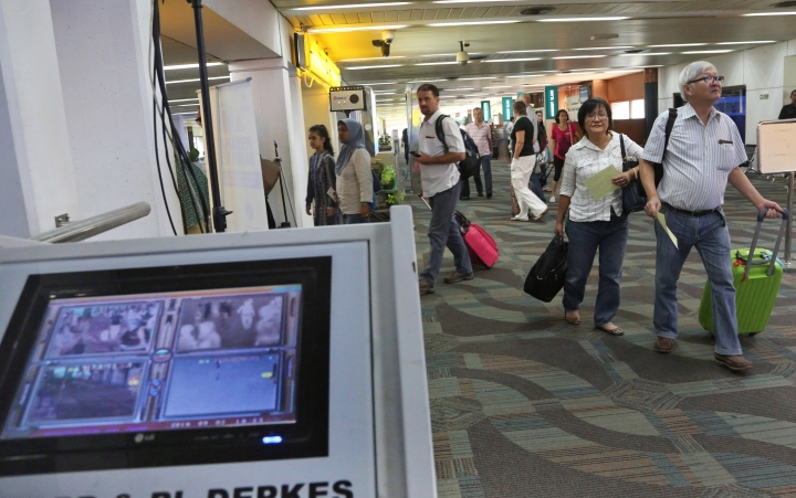 Arriving travelers walk past a thermal scanner at Soekarno-Hatta International Airport in Tangerang, Indonesia, Friday, Sept. 2, 2016. Indonesia is screening travelers from Singapore for the mosquito-borne Zika virus as the city-state reports a growing number of infections. (AP Photo/Tatan Syuflana)