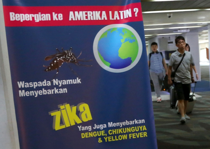 Arriving travelers walk past an nformation banner on Zika virus at Soekarno-Hatta International Airport in Tangerang, Indonesia, Friday, Sept. 2, 2016. Indonesia is screening travelers from Singapore for the mosquito-borne Zika virus as the city-state reports a growing number of infections. (AP Photo/Tatan Syuflana)