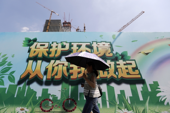 """A woman carrying an umbrella to protect from the sun as she walks past a billboard promoting environment protection on display near a construction site at the Central Business District of Beijing, Saturday, Sept. 3, 2016. China announced on Saturday that it has ratified the emissions-cutting agreement reached last year in Paris, giving a big boost to efforts to bring the accord into effect by the end of this year. The words on the billboard read """"Protect environment, start from you and me."""" (AP Photo/Andy Wong)"""