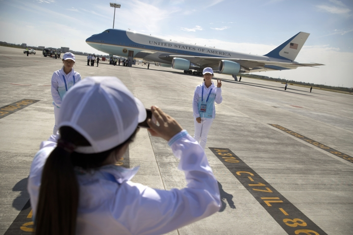 A Chinese volunteer poses for a photo in front of Air Force One after U.S. President Barack Obama arrived at the Hangzhou Xiaoshan International Airport, Saturday, Sept. 3, 2016, in Hangzhou, China, to attend the G-20 summit. Obama is expected to meet with China's President Xi Jinping Saturday afternoon. (AP Photo/Mark Schiefelbein)