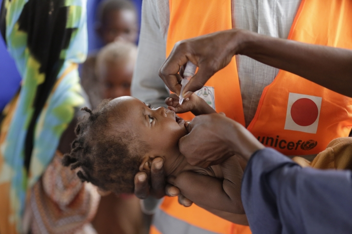 In this photo taken on Saturday, Aug. 27, 2016, a health official administers a polio vaccine to a child at a camp for people displaced by Islamist Extremist in Maiduguri, Nigeria. An emergency polio vaccination campaign aimed at reaching 25 million children this year has begun in parts of Nigeria newly freed from Boko Haram Islamic extremists, with fears that many more cases of the crippling disease are likely to be found. (AP Photo/Sunday Alamba)