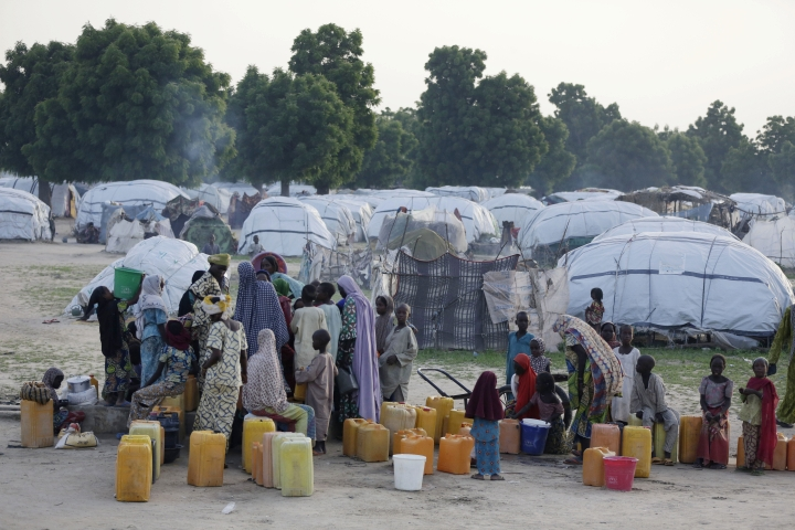 In this photo taken on Tuesday, Aug. 30, 2016, people displaced by Islamist Extremist fetch water at Muna camp in Maiduguri, Nigeria. An emergency polio vaccination campaign aimed at reaching 25 million children this year has begun in parts of Nigeria newly freed from Boko Haram Islamic extremists, with fears that many more cases of the crippling disease are likely to be found. (AP Photo/Sunday Alamba)