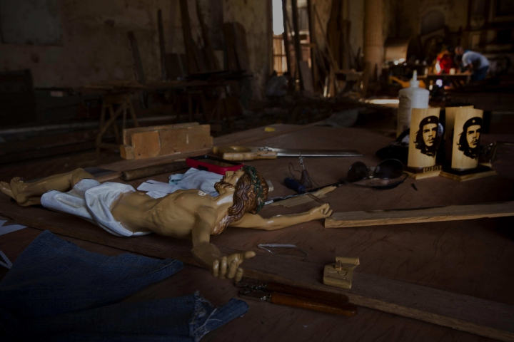 """In this Sept. 1, 2016 photo, images of revolutionary icon Ernesto """"Che"""" Guevara sit next to a wooden statue of Jesus Christ in a carpenters workshop at an old church building in Remedios, Cuba. By December of this year, US airlines will have some 300 direct flights a week scheduled from the U.S. to 10 cities across Cuba, like Santa Clara. (AP Photo/Ramon Espinosa)"""