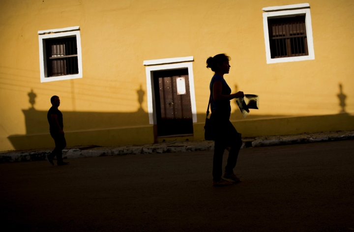 In this Sept. 1, 2016 photo, a woman walks holding a set of medical x-rays next to the village church in Remedios, Cuba. With U.S. commercial flights reestablished the Cuban government is welcoming the wave of new visitors and is struggling to update infrastructure that's already overwhelmed. (AP Photo/Ramon Espinosa)