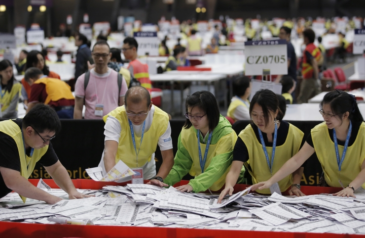 Electoral officers count ballots at the central ballot counting station for the legislative council elections in Hong Kong, Monday, Sept. 5, 2016. Hong Kong voted Sunday in the specially administered Chinese city's most crucial election since the handover from Britain in 1997, the outcome of which could pave the way for a fresh round of political confrontations over Beijing's control of the city. (AP Photo/Kin Cheung)