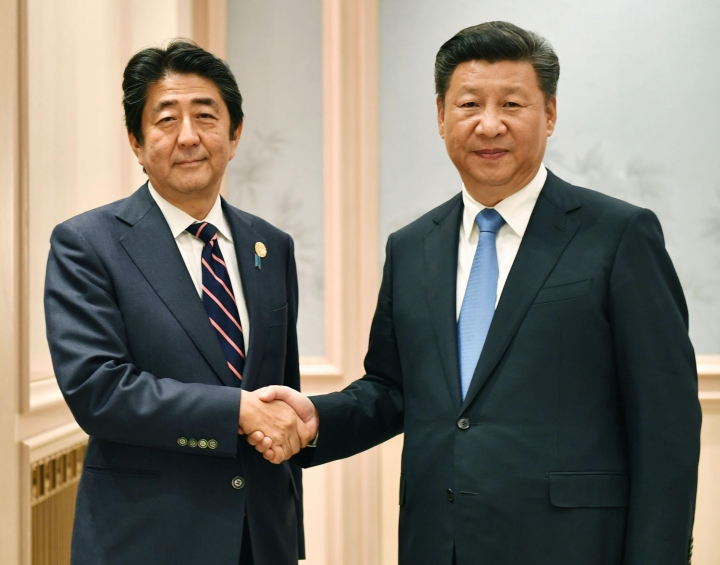 Chinese President Xi Jinping, right, and Japanese Prime Minister Shinzo Abe shake hands before their bilateral meeting, on the sideline of the G-20 Summit in Hangzhou, China, Monday, Sept. 5, 2016. (Kyodo News via AP)