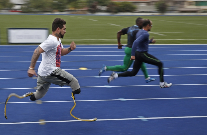 In this July 22, 2016 photo, athlete Alan Fonteles, from Brazil, left, who competes mainly in category T44, trains ahead the Paralympic Games athletics events in Sao Paulo, Brazil. Only a last-minute Brazilian government bailout has helped save the Paralympic Games from a shortfall in the local, privately funded operating budget. Almost everything will be scaled back: venues, seating, and staffing, but Paralympic officials say that no sports or nations have been cut out. (AP Photo/Andre Penner)