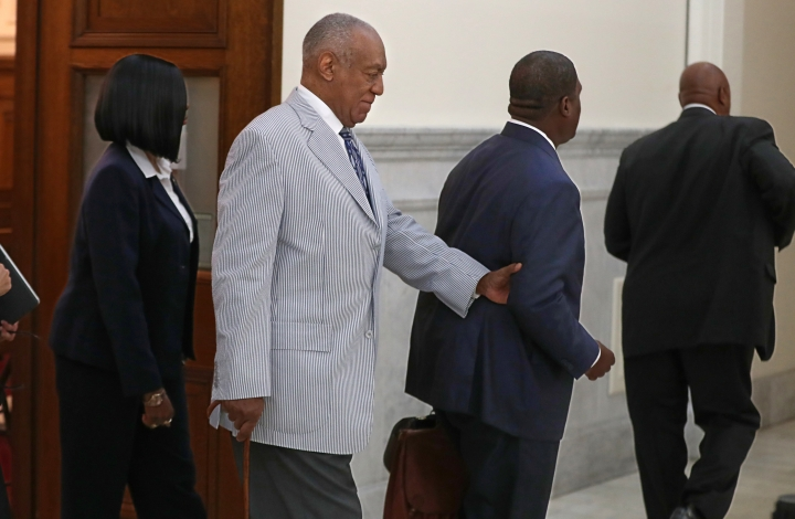 Bill Cosby, second from left, is led out of Courtroom A in the Montgomery County Courthouse, Tuesday, Sept. 6, 2016, in Norristown, Pa., by one of his aides after a pre-trial conference in his sexual assault case. Prosecutors said Tuesday that they want 13 other women, who said they were intoxicated when Cosby allegedly assaulted them, to testify at his upcoming felony sex assault trial. (Michael Bryant/The Philadelphia Inquirer via AP, Pool)