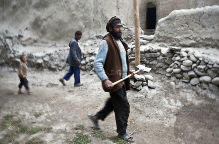 In this Aug. 18, 2016 photo, Saeed Beg, right, walks towards his home in Sarkand village, Wakhan district of Badakhshan province, far northeastern Afghanistan. Beg and his family live in a two-room mud house with no electricity or running water, no bathroom, no kitchen and no furniture apart from a few threadbare rugs and a couple of thin mattresses. Beg describes how he exchanges his sheep and goats for food -- rice, cooking oil, salt -- in the barter system that is the main form of financial transaction here in the shadow of the Hindu Kush. (AP Photos/Massoud Hossaini)