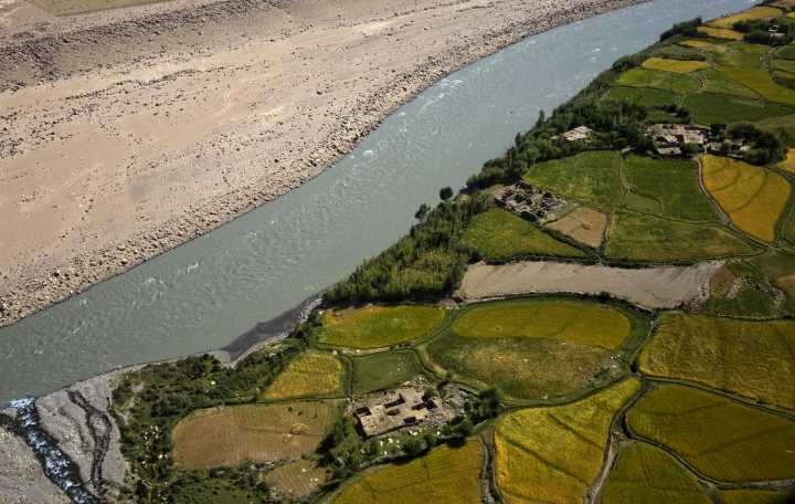 This Aug. 15, 2016 photo, shows part of the town of Ishkashim along the Amu Darya river that divides Afghanistan, right, from Tajikistan, in Badakhshan province, far northeastern Afghanistan. The region is home to around 17,000 Ismailis, followers of the Aga Khan, one of the world's wealthiest men and their hereditary spiritual leader for 49 generations. But it is so poor, even for Afghanistan, that people borrow food and children go barefoot during the long, harsh winters. (AP Photo/Massoud Hossaini)