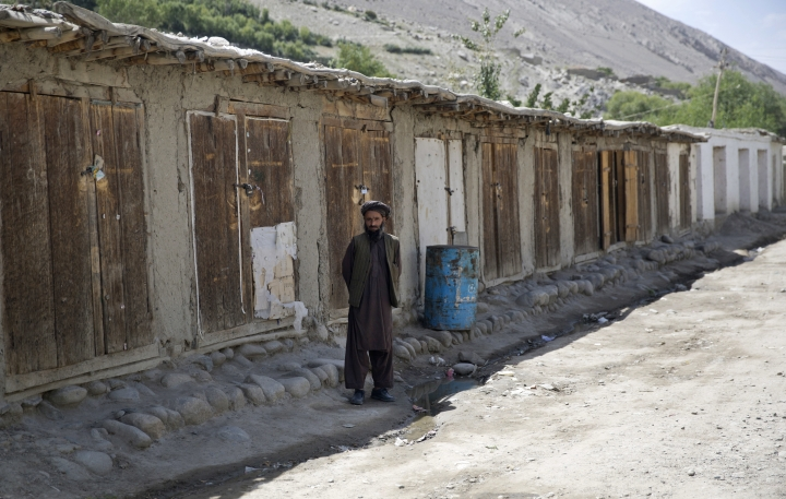 In this Aug. 18, 2016 photo, a villager stands in front of closed shops in Qazideh village, Wakhan district of Badakhshan province, far northeastern Afghanistan. The Wakhan corridor, which has been named Afghanistan's second national park, is the country's most -- perhaps only -- peaceful region. But it is so poor, even for Afghanistan, that people borrow food and children go barefoot during the long, harsh winters. (AP Photos/Massoud Hossaini)