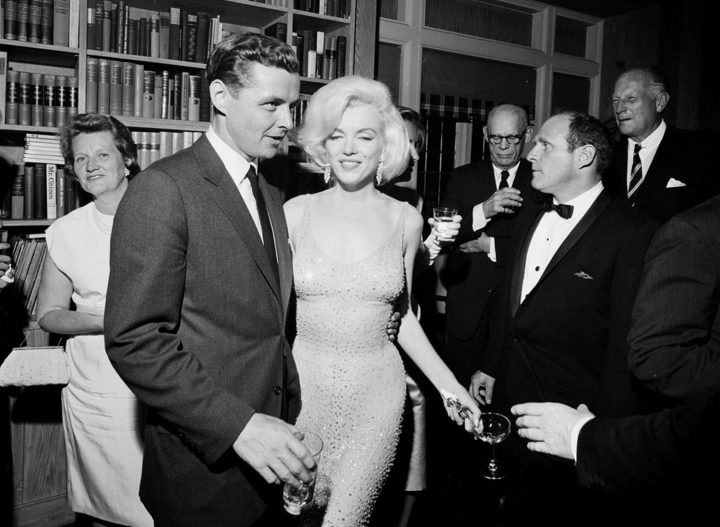 """In this May 19, 1962 photo provided by the John F. Kennedy Presidential Library and Museum, actress Marilyn Monroe wears the iconic gown that she wore while singing """"Happy Birthday"""" to President John F. Kennedy at Madison Square Garden, during a reception in New York City. Standing next to Monroe is Steve Smith, President Kennedy's brother-in-law. Julien's Auctions will offer Monroe's gown at auction in Los Angeles on Nov. 17, 2016. (Cecil Stoughton/White House Photographs, John F. Kennedy Presidential Library and Museum via AP)"""