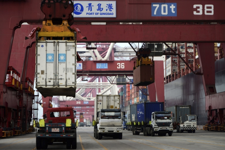 Containers are loaded onto a cargo ship for export at a port in Qingdao in east China's Shandong province, Thursday Sept. 08, 2016. China's exports rose in August for the first time in two years, while the contraction in imports narrowed in a positive sign for global economic growth. (Chinatopix via AP)