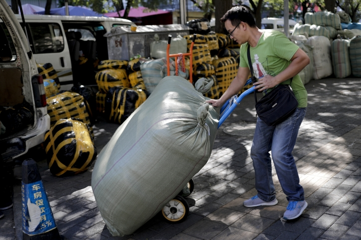 A worker loads goods for his customer from a pick-up station near a clothing wholesale market in Beijing, China, Thursday, Sept. 8, 2016. China's exports rose in August for the first time in two years, while the contraction in imports narrowed in a positive sign for global economic growth. (AP Photo/Andy Wong)