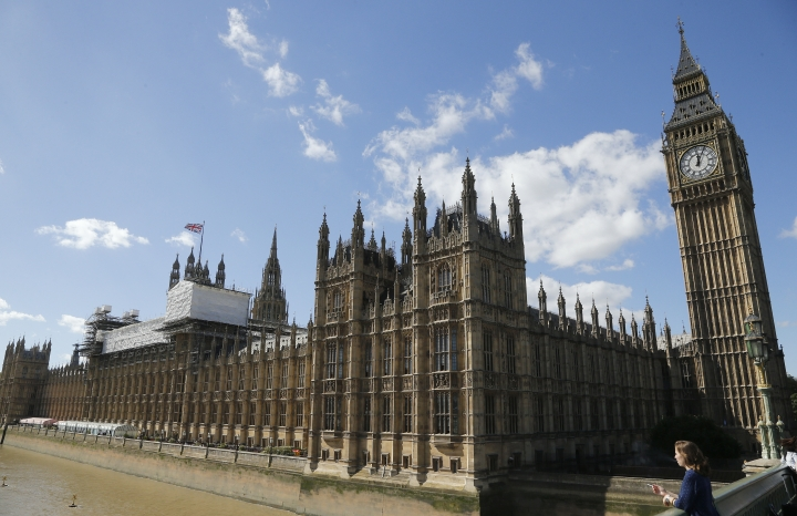 General view of the Houses of Parliament with scaffolding erected around a section of it in London, Thursday, Sept. 8, 2016. A committee charged with stopping Britain's creaky, leaky Parliament from falling down is set to say whether lawmakers will have to move out for several years so repair work can be done. The Joint Committee on the Palace of Westminster has been studying options for the 19th-century complex, which needs work to repair collapsing roofs, crumbling walls and leaking pipes, and to remove asbestos. (AP Photo/Frank Augstein)