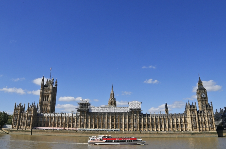General view of the Houses of Parliament with scaffolding around a section of it in London, Thursday, Sept. 8, 2016. A committee charged with stopping Britain's creaky, leaky Parliament from falling down is set to say whether lawmakers will have to move out for several years so repair work can be done. The Joint Committee on the Palace of Westminster has been studying options for the 19th-century complex, which needs work to repair collapsing roofs, crumbling walls and leaking pipes, and to remove asbestos. (AP Photo/Frank Augstein)