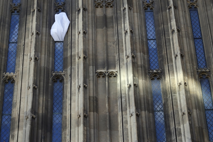 Wind blows the curtain out of a window at the Houses of Parliament in London, Thursday, Sept. 8, 2016. A committee charged with stopping Britain's creaky, leaky Parliament from falling down is set to say whether lawmakers will have to move out for several years so repair work can be done. The Joint Committee on the Palace of Westminster has been studying options for the 19th-century complex, which needs work to repair collapsing roofs, crumbling walls and leaking pipes, and to remove asbestos. (AP Photo/Frank Augstein)