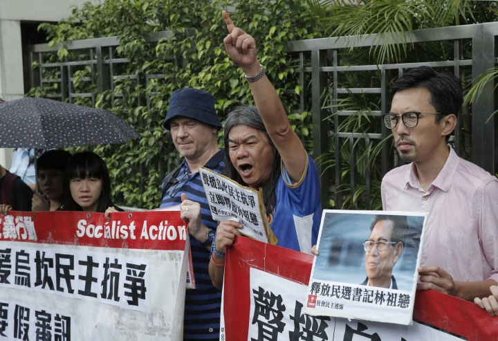 """Radical pro-democracy lawmaker Leung Kwok-hung, second from right, and other protesters holding a picture of Wukan village's leader Lin Zuluan during a demonstration outside the Chinese central government's liaison office in Hong kong, Friday, Sept. 9, 2016. The democratically elected mayor of the fishing village in southern China - which became the center of international attention five years ago for protests against land seizures - has been given three years in jail on bribery charges. The Chinese words on placard read: """"Release democratically elected secretary Lin Zuluan."""" (AP Photo/Kin Cheung)"""