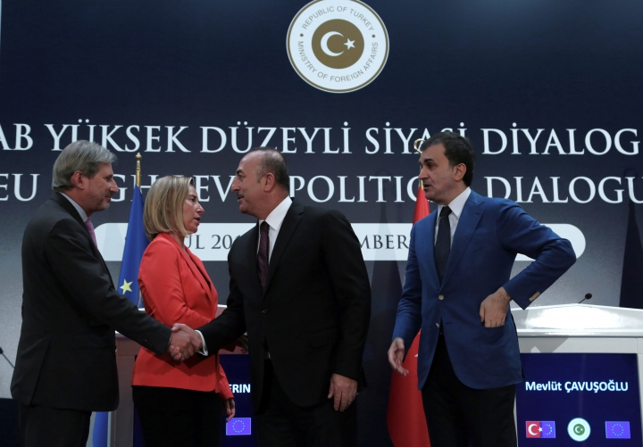 European Union's Foreign Policy Chief Federica Mogherini, second left, EU Enlargement Commissioner Johannes Hahn, left, Turkey's Foreign Minister Mevlut Cavusoglu, second right, and Turkey's EU Minister Omer Celik shake hands after a joint news conference in Ankara, Turkey, Friday, Sept. 9, 2016. Mogherini says the 28-member bloc and Turkey agree that there can be no military solution to the Syrian conflict and that only a political solution can bring peace to the war-torn country.(AP Photo/Burhan Ozbilici)