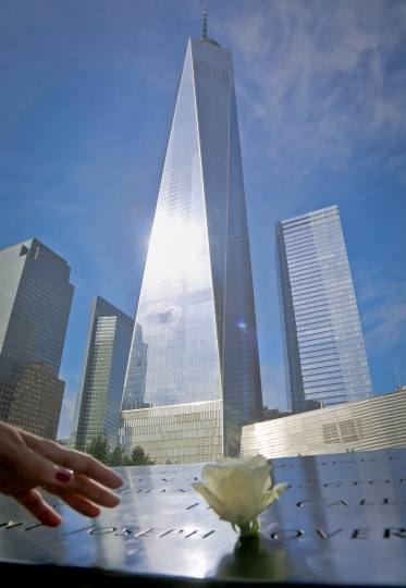 A visitor reaches to touch a name engraved at the Sept. 11 memorial site to remember the victims of the 2001 attacks on the World Trade Center, Thursday Sept. 8, 2016, in New York. Sunday marks the 15th anniversary of the terror attacks. (AP Photo/Bebeto Matthews)