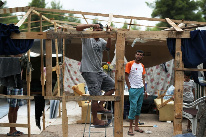A Syrian man hammers a nail on woods as he prepares his family tent for winter at Ritsona refugee camp north of Athens, which hosts about 600 refugees and migrants on Thursday, Sept. 8, 2016. The refugee crisis is expected to be a central issue in discussions Friday at a meeting in Athens of leaders from Mediterranean countries in the European Union. (AP Photo/Petros Giannakouris)