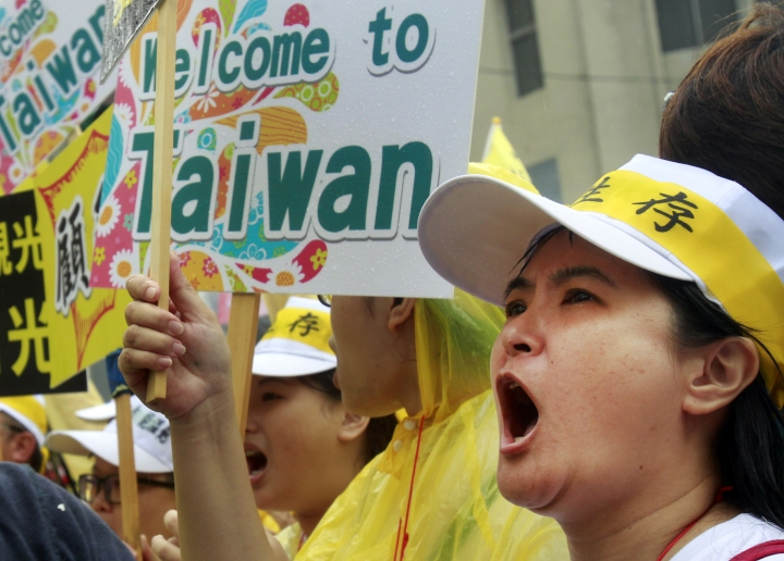 """A tourism industry worker shoots in front a slogan reading """"Welcome to Taiwan"""" during a march in Taipei, Taiwan, Monday, Sept. 13, 2016. Thousands of tourism industry workers held a march to call for the government''s attention on the decline of mainland Chinese visitors since President Tsai Ing-wen took office in May. It''s believed that Beijing might have taken the action to tighten its control over Taiwan-bound tourist arrivals after Tsai refused to endorse the concept of a single Chinese nation. (AP Photo/Chiang Ying-ying)"""