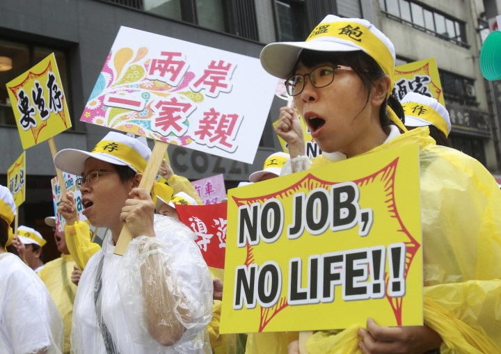 """Tourism industry workers shout and hold slogans reading """"No job. No life!"""" and """"Taiwan and Mainland are related"""" during a march in Taipei, Taiwan, Monday, Sept. 13, 2016. Thousands of tourism industry workers held a march to call for the government''s attention on the decline of mainland Chinese visitors since President Tsai Ing-wen took office in May. It''s believed that Beijing might have taken the action to tighten its control over Taiwan-bound tourist arrivals after Tsai refused to endorse the concept of a single Chinese nation. (AP Photo/Chiang Ying-ying)"""