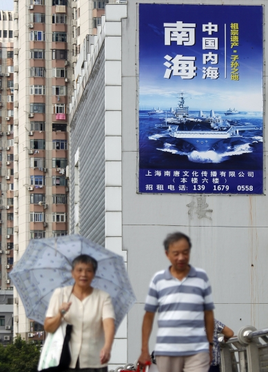 """People walk past a poster that reads """"The South China Sea is China's inland sea"""" in Shanghai, China, Monday, Sept. 12, 2016. The Chinese and Russian navies launched eight days of war games in the South China Sea on Monday, in a sign of growing cooperation between their armed forces against the backdrop of regional territorial disputes. (Chinatopix via AP)"""