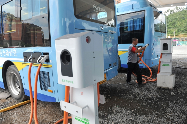In this Friday, July 15, 2016, photo, a driver charges an electric bus made by King Long United Automotive Industry at a terminal in Lin'an city in eastern China's Zhejiang Province. China's electric vehicle industry, a flagship for Beijing's technology ambitions, has been rocked by scandal after five companies were caught collecting millions of dollars in subsidies for buses they never made. (Chinatopix via AP)