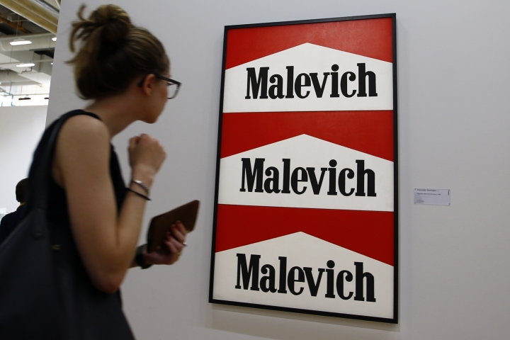 "In this photo dated Monday, Sept. 12, 2016 a visitor looks on ""Triptyque Malevitch-Marlboro, 1985"" by Alexander Kosolapov (1943) during the presentation of the Kollektsia exhibition dedicated to Russian contemporary art at Beaubourg Museum in Paris, France. One of the richest oligarchs in Russia, Vladimir Potanin, is donating over 250 works of Russian and Soviet art to France national modern art museum, the Pompidou Center, to promote cultural understanding. The exhibition runs through Sept. 14, 2016 to March 27, 2017. (AP Photo/Francois Mori)"