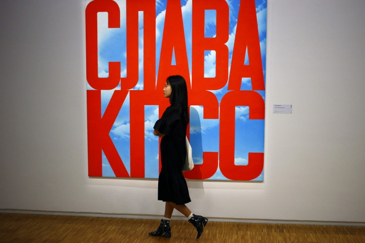 "In this photo dated Monday, Sept. 12, 2016 a visitor passes by an oil painting ""Gloire au PCUS, 2003-2005"" by Erik Bulatov (1933) during the presentation of the Kollektsia exhibition dedicated to Russian contemporary art at Beaubourg Museum in Paris, France. One of the richest oligarchs in Russia, Vladimir Potanin, is donating over 250 works of Russian and Soviet art to France national modern art museum, the Pompidou Center, to promote cultural understanding. The exhibition runs through Sept. 14, 2016 to March 27, 2017. (AP Photo/Francois Mori)"