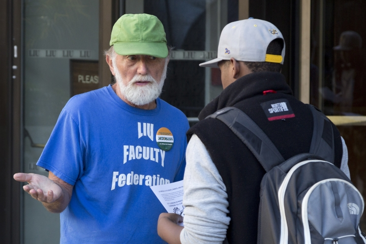 Glen Lawrence, left, a professor of chemistry and biochemistry, talks with a student at Long Island University's Brooklyn campus, Tuesday, Sept. 13, 2016 in New York. Hundreds of professors have been locked out of their classrooms because of a labor dispute, forcing students to take classes with replacement teachers rushed into service at the start of the school year. (AP Photo/Mark Lennihan)