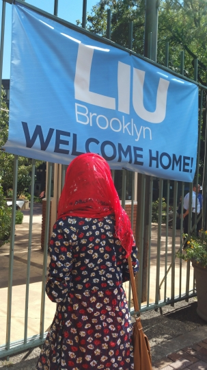 """A student who preferred not to be identified looks up at a """"Welcome"""" sign hung from the fence at the Long Island University campus in the Brooklyn borough of New York, Tuesday, Sept. 13, 2016. Students at the New York City campus say they have begun the school year with classes being taught by replacement teachers of questionable quality after the administration locked out their regular professors as part of a bitter labor dispute. (AP Photo/Verena Dobnik)"""